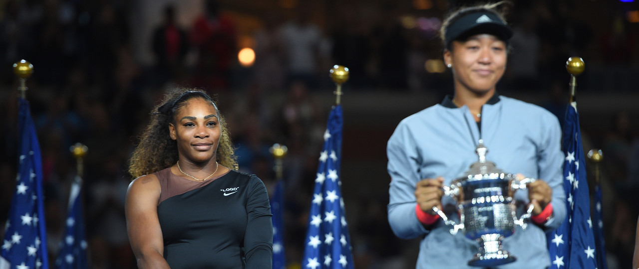Serena Williams looking at Naomi Osaka on the podium at US Open 2018