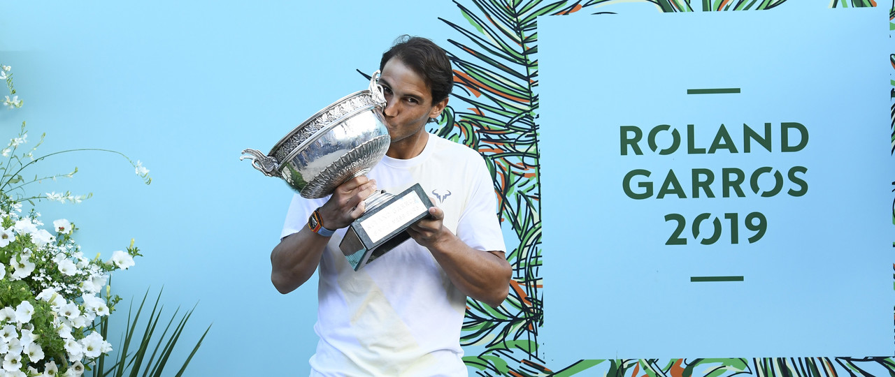 Rafael Nadal kissing his Roland-Garros 2019 trophy in front of the RG19 wall.